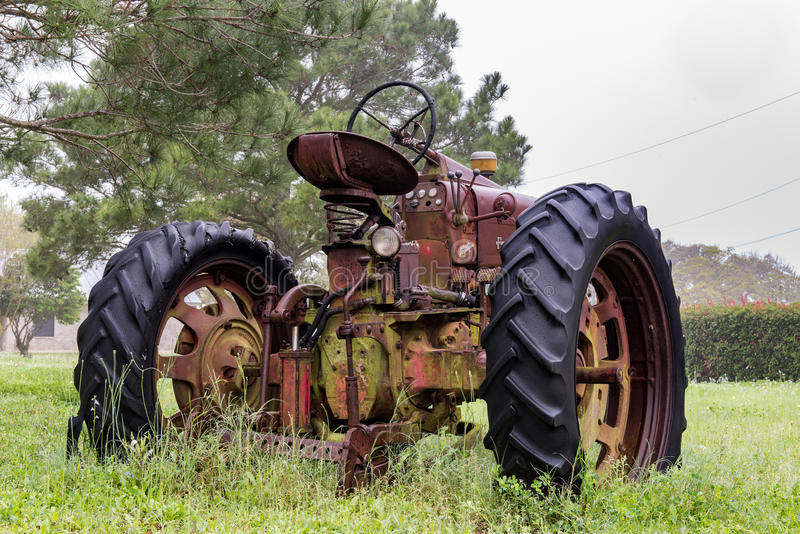 Old abandoned tractor sitting in the rain royalty free stock images