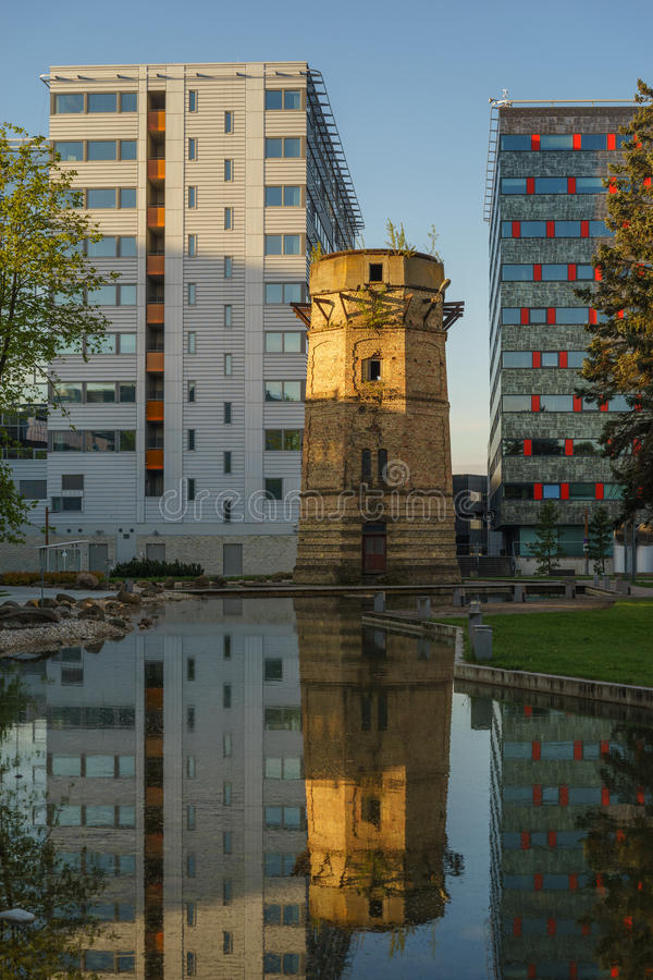 Old abandoned water-tower and modern business building royalty free stock image