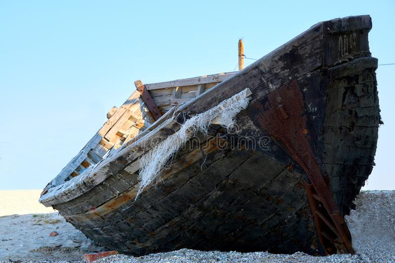 Old abandoned wooden fishing boat with rusted nails by the sea stock photo