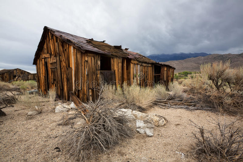 Old Abandoned Wooden Shack in Desert with Stormy Sky. A landscape view of an old abandoned wooden shack run down and ruined by the elements over time royalty free stock photography