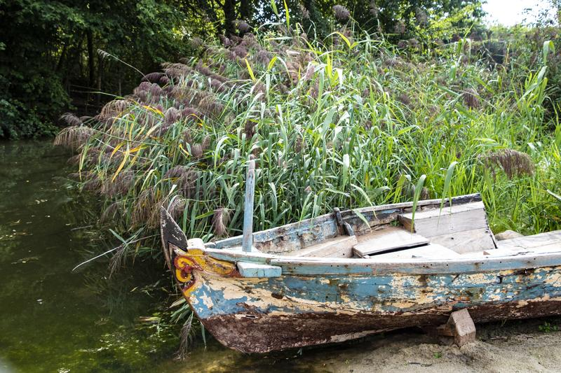 Old abandoned wrecked fishing boat at a lake stock photography