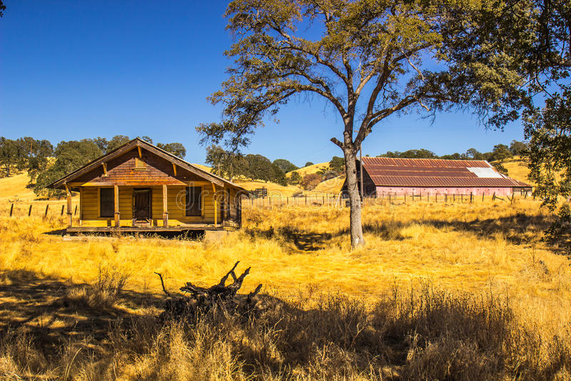 Old Abandoned Yellow Farm House With Large Barn In Gackground royalty free stock photo