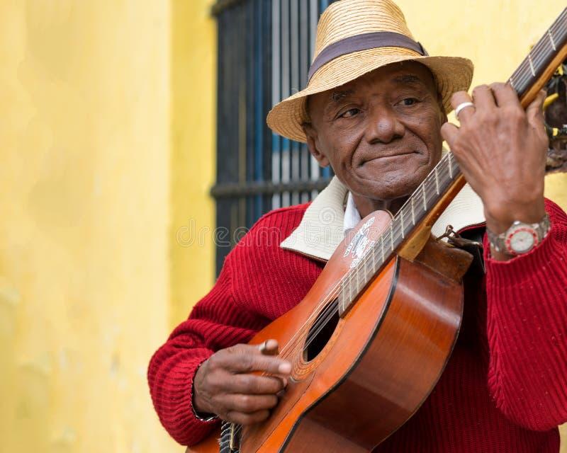 Old afrocuban street musician playing the guitar in Havana stock photo