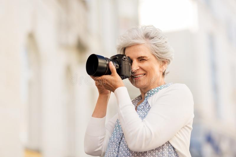 Senior woman photographing by digital camera. Old age, photography and people concept - happy senior woman photographing by digital camera on city street stock images