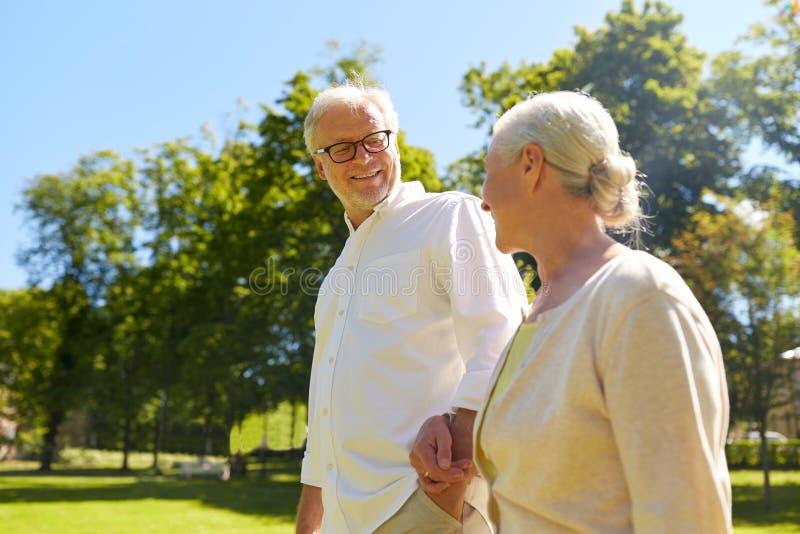 Happy senior couple walking at summer city park royalty free stock images