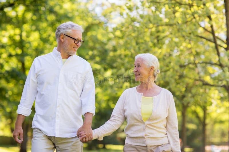 Happy senior couple walking at summer park stock photo