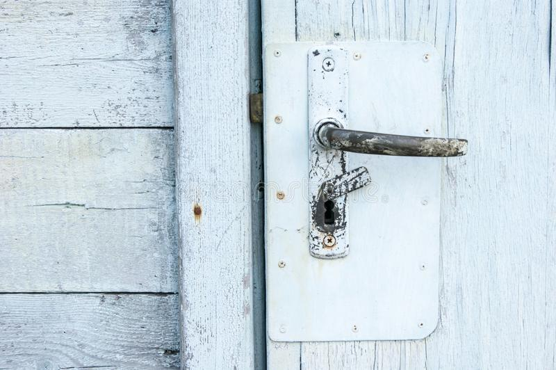 Old age, vintage, shabby painted wood - old white door and metal door handle, entrance stock photography