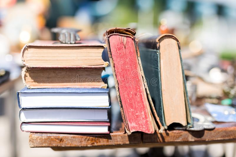 Old aged books at flea market. Vintage retro literature on wooden table outdoors. Street swap meet background royalty free stock image