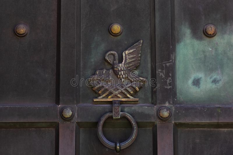 Old aged ornamented knocker as nest with bird and nestlings. Metalic door of Cathedral in Fredrikstad Norway. Old aged ornamented knocker as nest with bird and royalty free stock photography