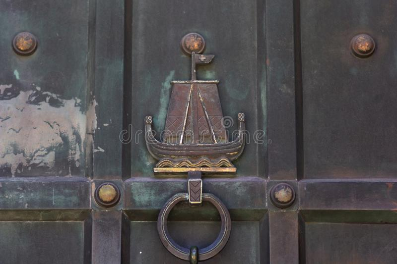 Old aged ornamented knocker as ship. Metalic door of Cathedral in Fredrikstad Norway. Old aged ornamented knocker as ship. Metalic door of the Cathedral in stock photography