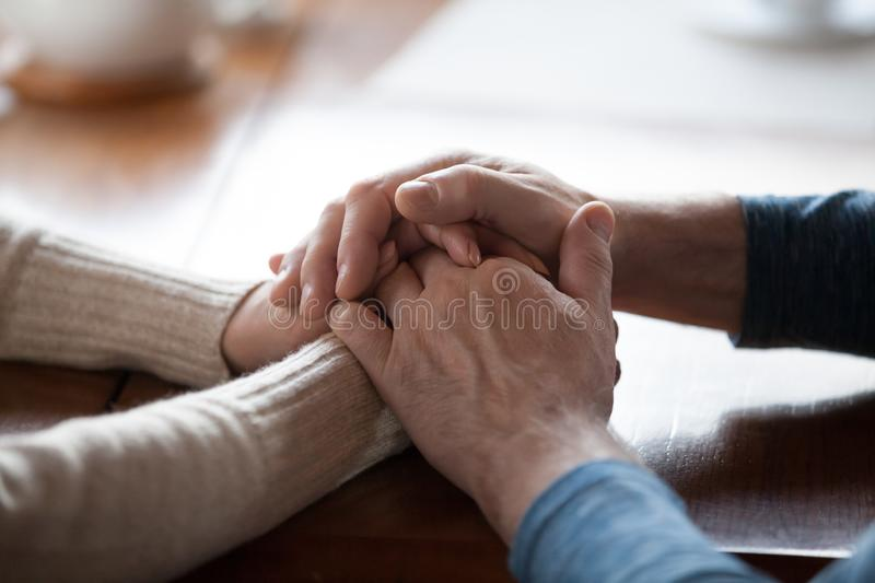 Old aged people holding hands close up view, support concept stock photo
