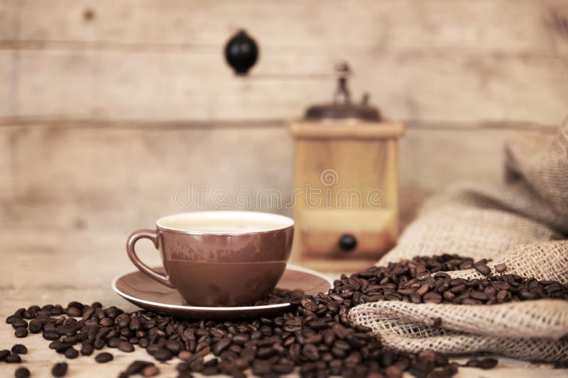 Old aged still life on coffee beans, cup and coffee grinder stock image