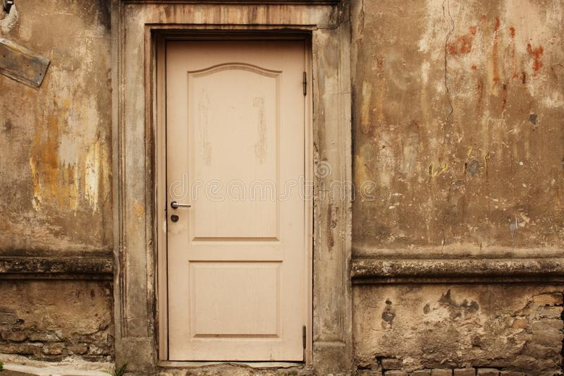 Old aged white door in weathered dirty wall royalty free stock photos
