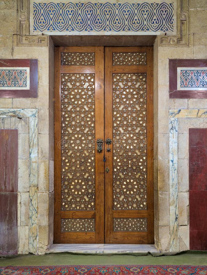 Old aged wooden closed door decorated with arabesque ornaments royalty free stock image