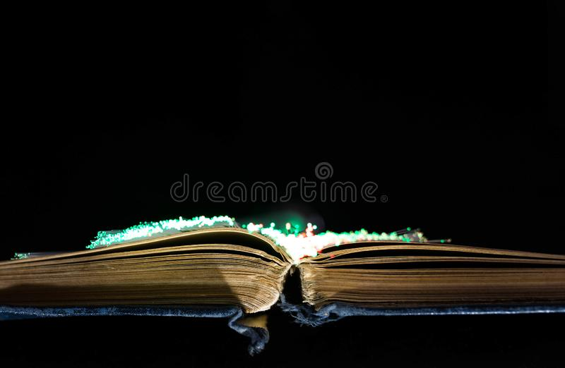 Old , aged, yellow opened book, glowing optical fibres. On black background, copy space royalty free stock image