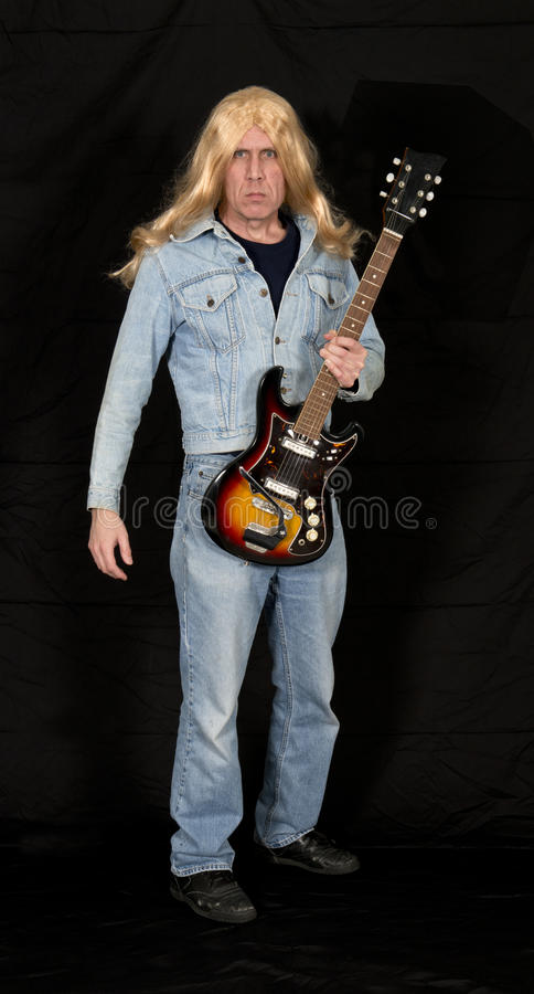 Old Aging Rock and Roll Star, Musician, Music Man. An old, aging rock and roll star struts his stuff with his electric guitar. The man still has long, blond hair stock photography