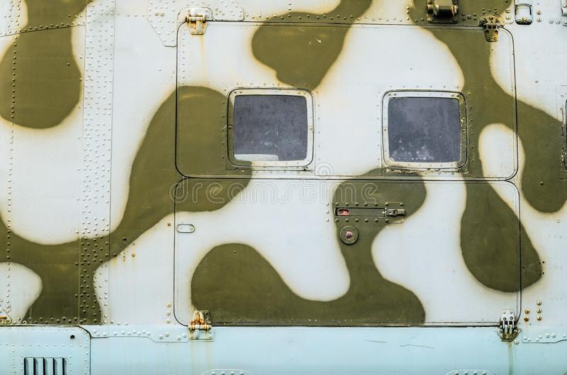 Old aircraft fuselage close up. Door handle and rivets. Part of the fuselage of a combat helicopter stock photography