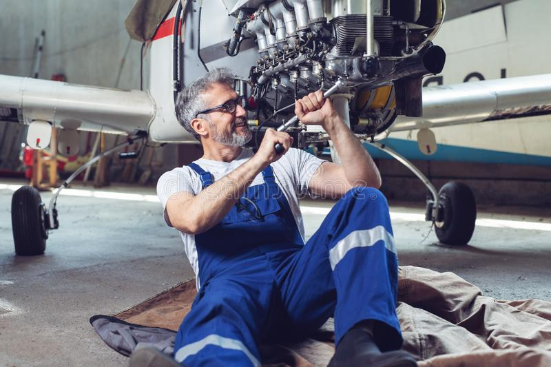 Aircraft mechanic repairs an aircraft engine in an airport hangar. Old Aircraft mechanic repairs an aircraft engine in an airport hangar royalty free stock images