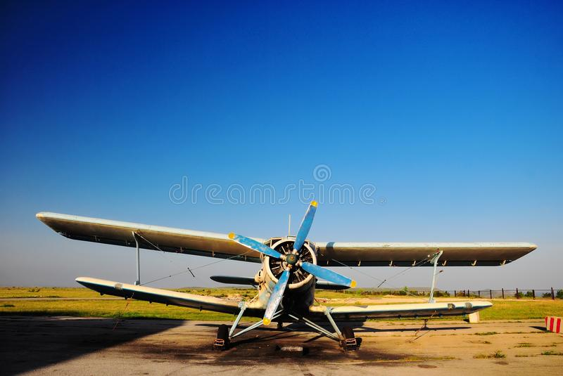 Old airplane biplane at the airport. Old light aircraft biplane on the airfield against a clear blue sky royalty free stock image