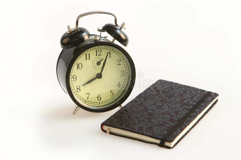 Old alarm clock and black diary stock images