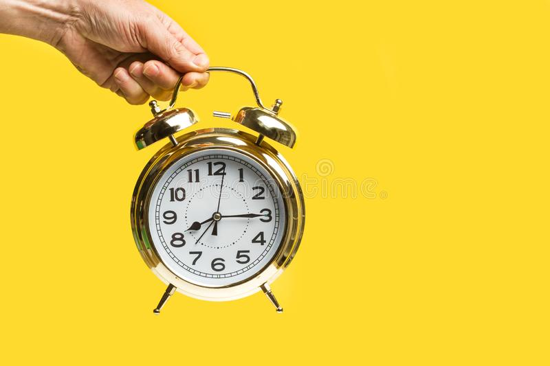 An old alarm clock in a a man hand royalty free stock image