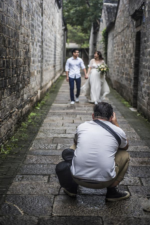 In an old alley in the east gate of Laomen, a photographer taking a wedding photo stock photo