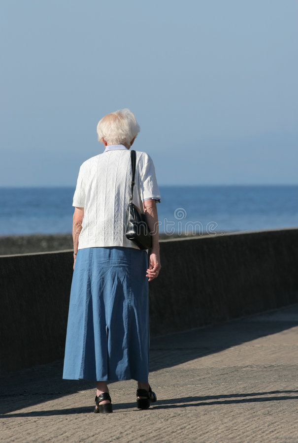 Old and Alone. Rear view of an elderly female walking alone on a beach promenade with the sea, out of focus, to the rear stock photo