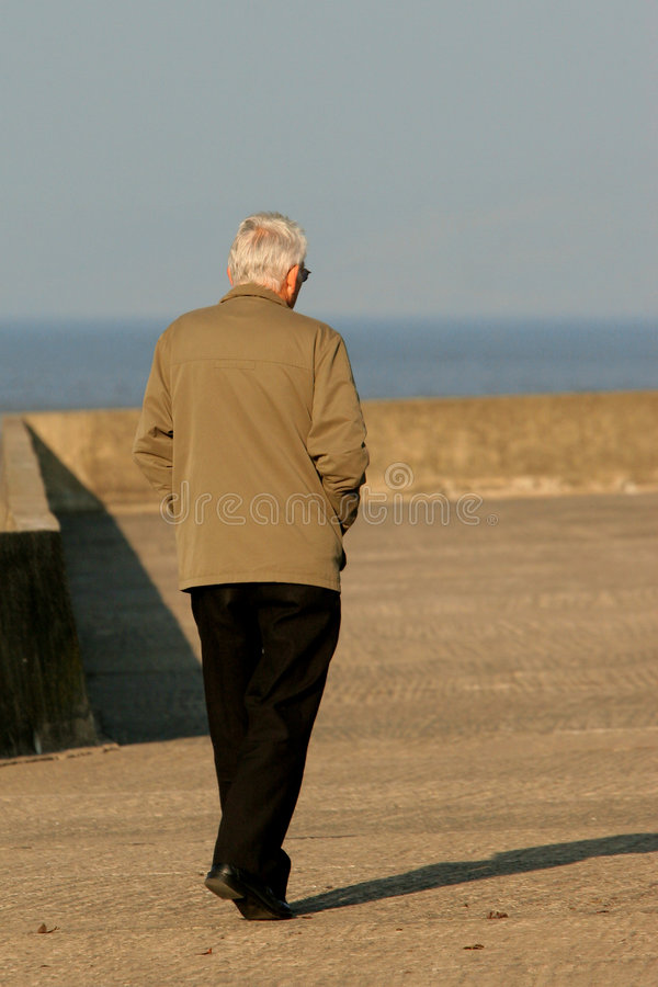 Old and Alone. Elderly man walking along a promenade stock photography