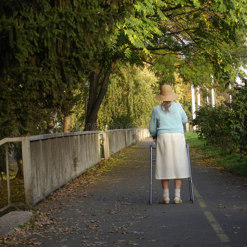 Old and alone lady. Old and handicapped lady walking slowly on the sunny autumn day stock photography