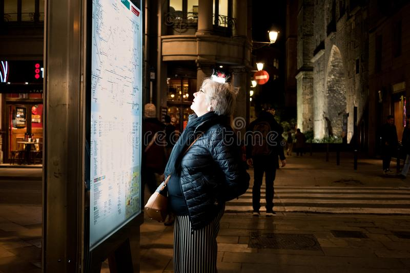 Barcelona, Spain - 19 december 2018: old lonely woman travelling solo looking at map of metro by night royalty free stock image