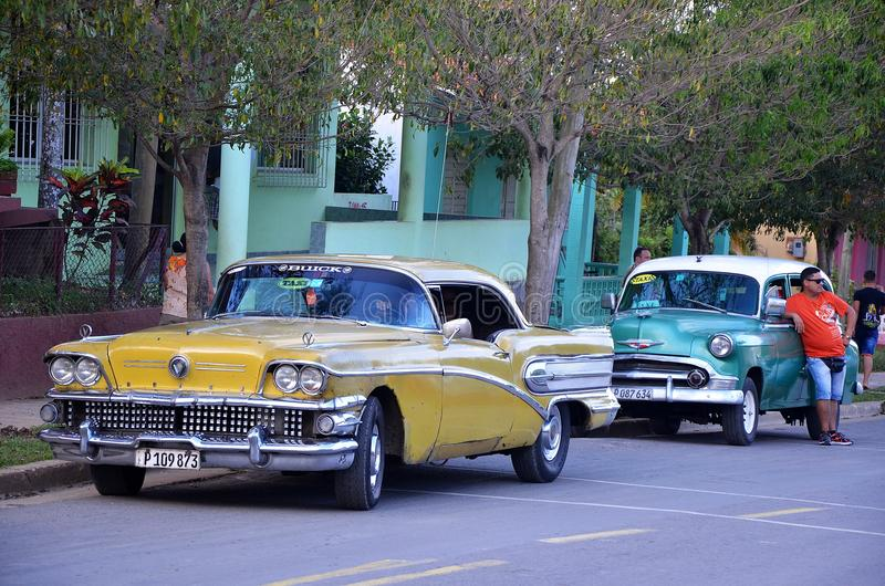 Old American cars in Vinales, Cuba. Chevrolets, cadillacs - with the taxi driver waiting for customers, Vinales, Cuba royalty free stock images