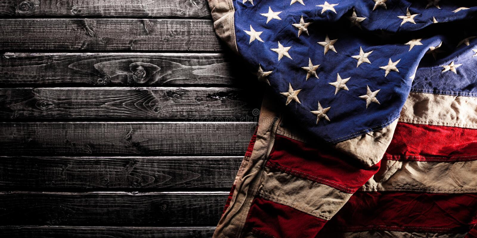 Old American flag on dark wooden background royalty free stock photo