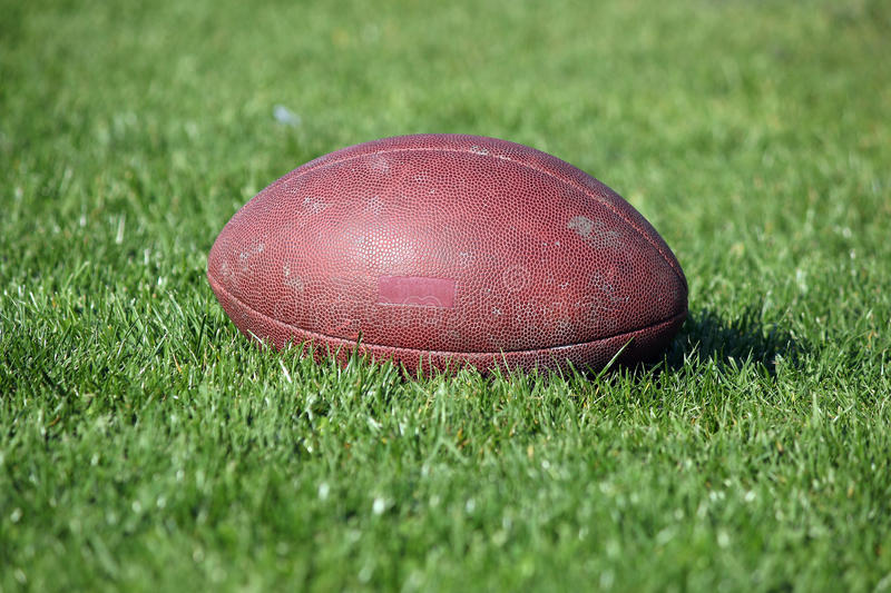 Old American football ball. On green grass royalty free stock photos