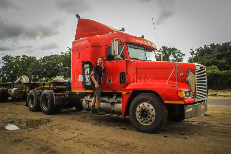 Old American red truck and young male hitchhiker on a dirt road. In Africa royalty free stock photography