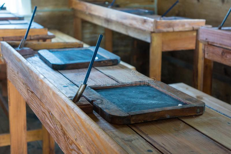 Old Americana School Room. Old classroom with antique chairs and desks with little slate tablets on desks for writing in chalk royalty free stock photography