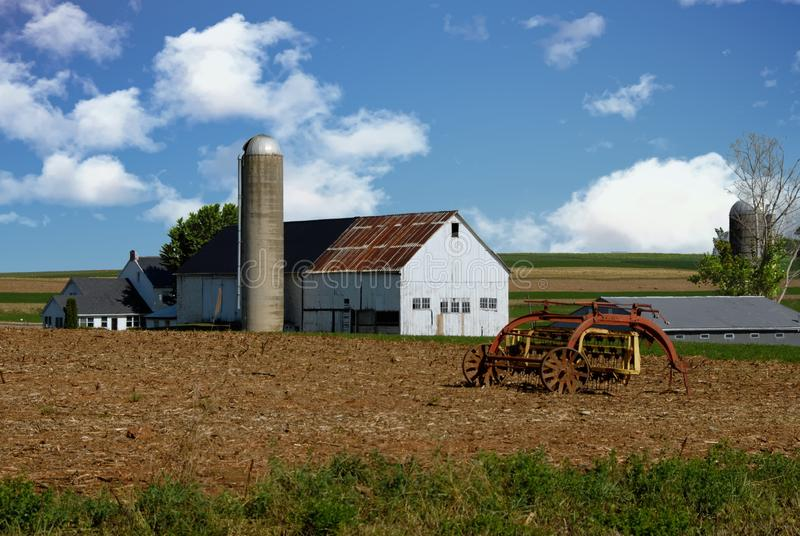 Old Amish White Wooden Barn and Farm Equipment. On a Sunny Summer Day royalty free stock image