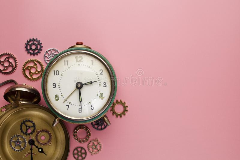 Old analog alarm clock and small parts of the watch on a pink background royalty free stock photography