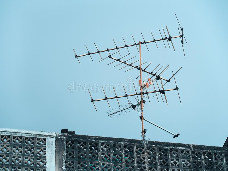 Old analog antenna for TV with blue sky background. Vintage color fitter with place your text. Bangkok, Thailand royalty free stock photo