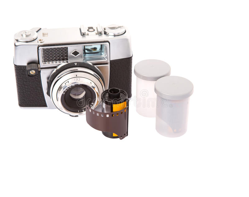 Old Analog Camera And Film Roll II. Old retro analog camera with new film roll over white background royalty free stock photography