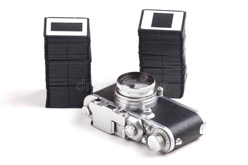 Old analog Camera and Stack of slides. Over white background royalty free stock photo