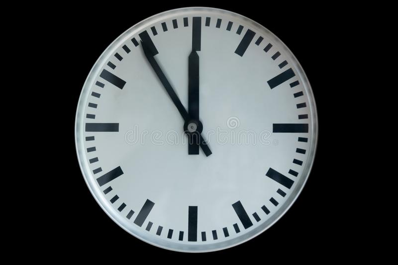 Old analog clock showing five to twelve isolated on black. Background royalty free stock images