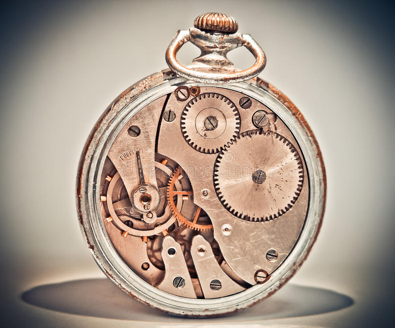 Old analog clocks seem unusual. Old analog clocks unusual look from the mechanism where the spinning gear on a gray background royalty free stock images