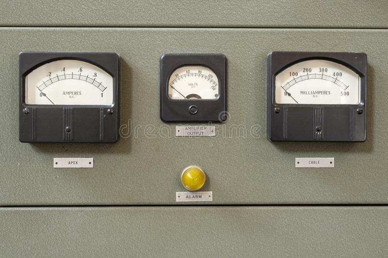 Old analog dial. Analog dials on wall panels showing D. C. current and volts stock photos
