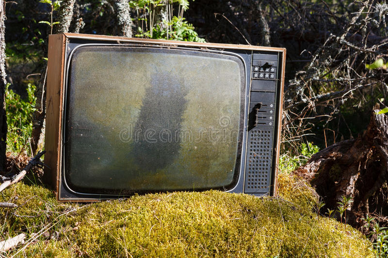 Old analog television in forest. Old abandoned analog television in forest royalty free stock photos