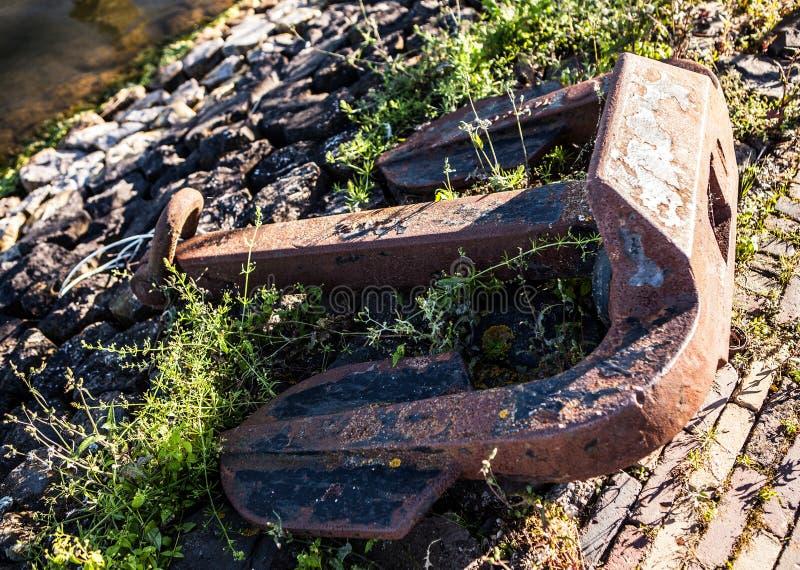 Old anchor on sea coast, large rusty heavy anchor stock photo