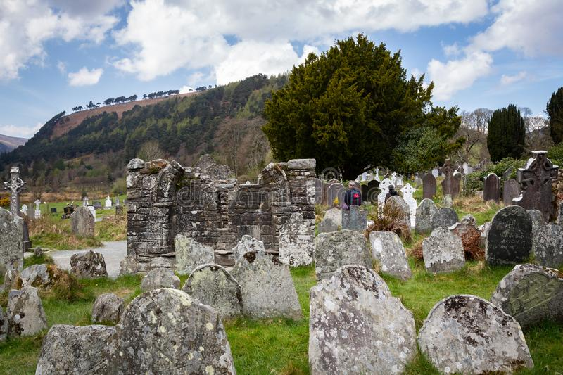 Old ancient cemetery with worn tombstones and mountain hill with cloudy sky. stock image