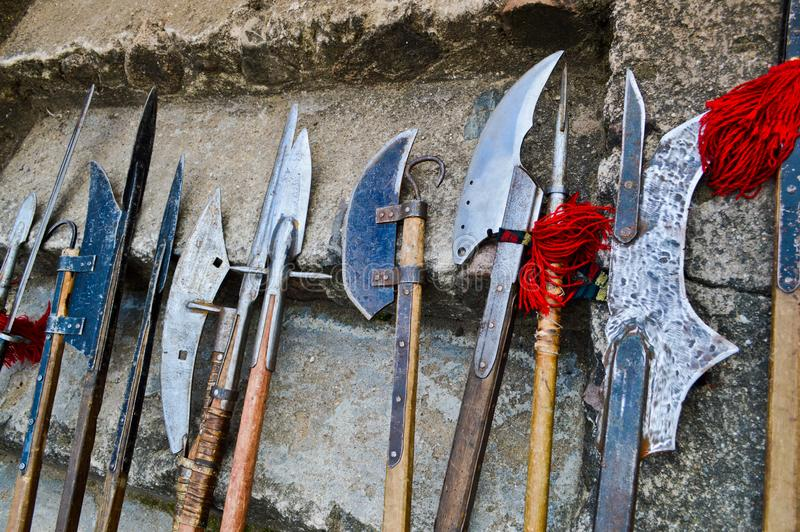 The old ancient medieval cold weapons, axes, olibards, knives, swords with wooden handles lick on the stone steps of the castle.  stock photo