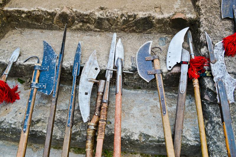 The old ancient medieval cold weapons, axes, olibards, knives, swords with wooden handles lick on the stone steps of the castle.  stock images