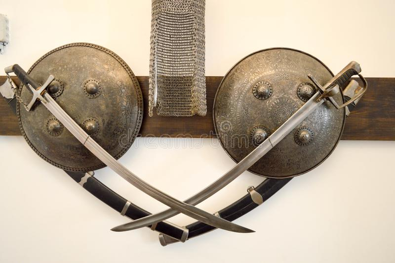 Old ancient medieval sharp dangerous combat captured swords, sabers, edged weapons and armor, shields royalty free stock photography