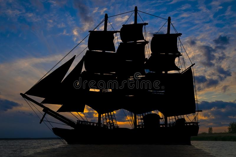 Old ancient pirate ship silhouette on peaceful ocean at sunset background royalty free stock photos